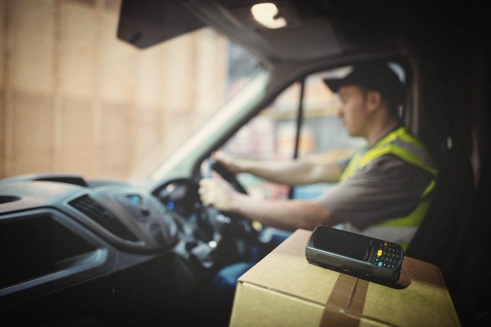 Delivery driver driving van with parcels on seat outside warehouse-375846-edited